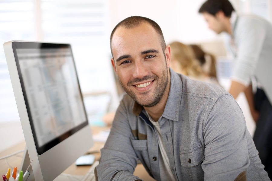 bigstock Cheerful guy sitting in front 53542399 - Importance of Wellbeing in the Workplace